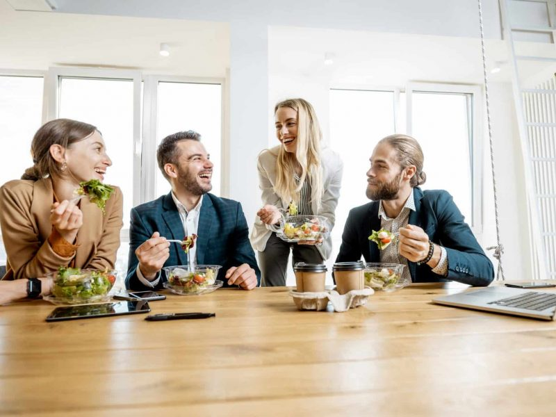 Group Of A Young Office Workers Eating Salads And Drinking Coffe