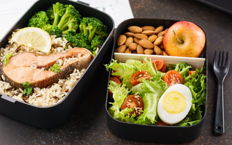 Takeaway Lunch Boxes With Food At Working Desk With Laptop.